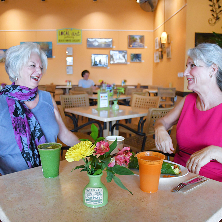 two women seating in Nature's Food Patch Cafe smiling, eating and drinking beverages
