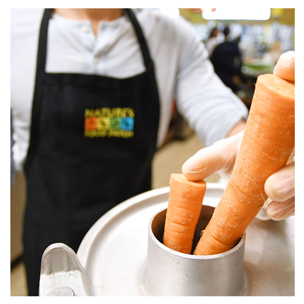 man with nature's food patch apron juicing carrot with gloves on