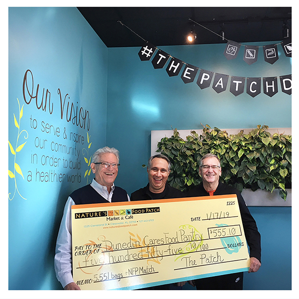 Three men holding large check donation to Dunedin Cares Food Pantry at Nature's Food Patch