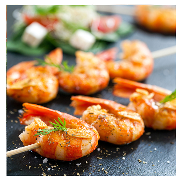 cooked shrimp on a skewer with a black background and greenery