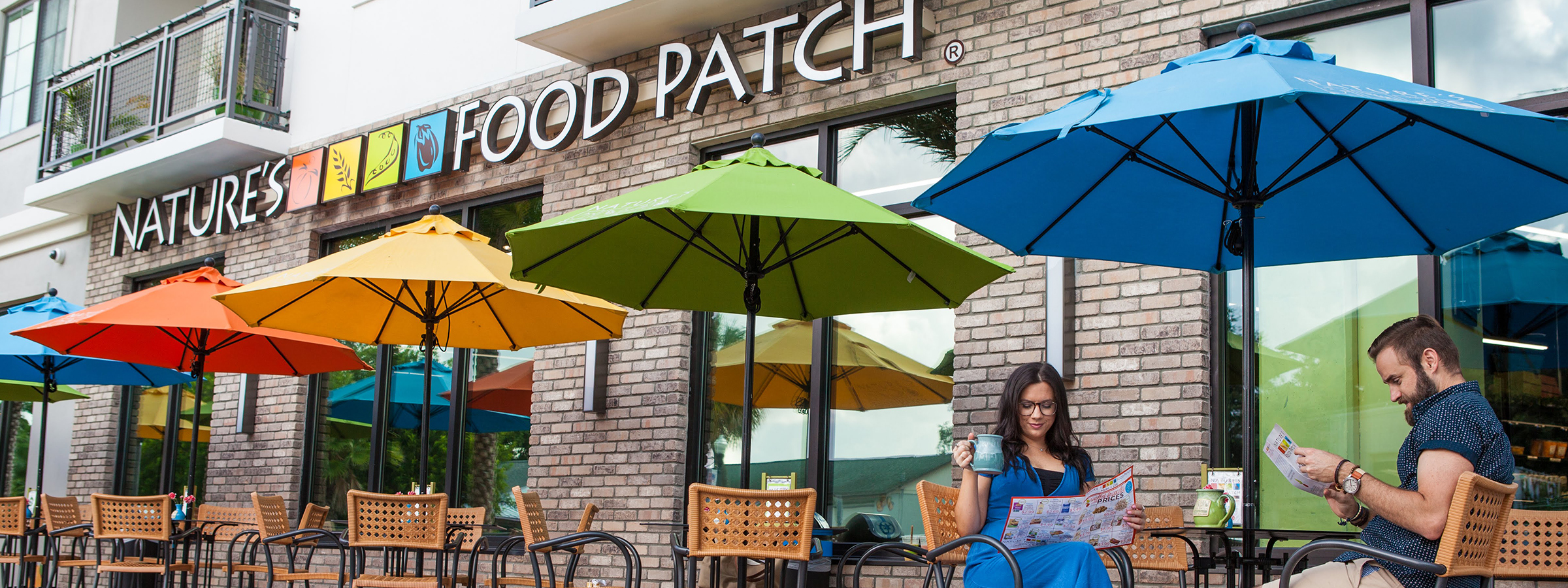 Our Story Blog - Nature's Food Patch with two people sitting outside under colorful umbrellas drinking coffee